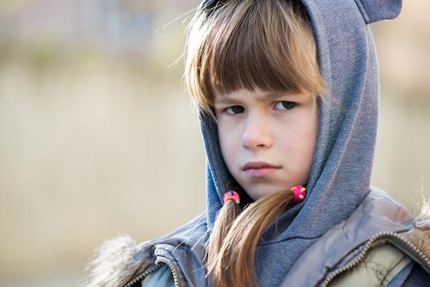 Портрет девушки счастливого ребенка в теплую одежду осенью на открытом воздухе.