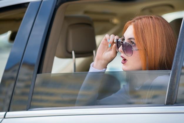 Молодая женщина с рыжими волосами и солнцезащитные очки, путешествуя на машине. пассажир, глядя из заднего стекла такси в городе.