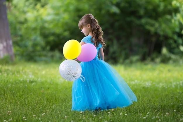 ぼやけた緑の木々に咲くフィールドに立っているカラフルな風船と長い青いドレスでかわいい金髪の長い髪の少女のプロフィールの全身肖像画