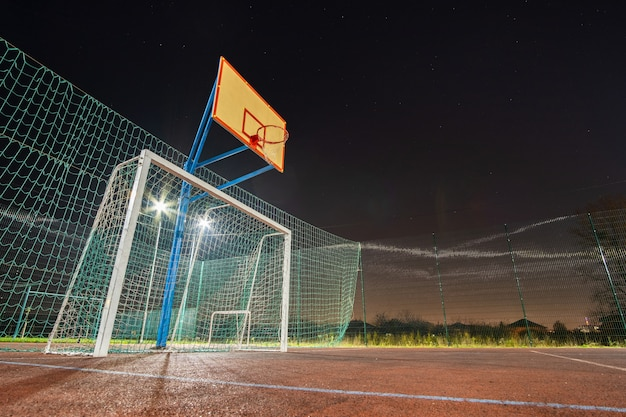 На открытом воздухе площадка для мини-футбола и баскетбола с воротами для мячей и корзиной, окруженной высоким защитным забором, ярко освещенным прожекторами ночью.
