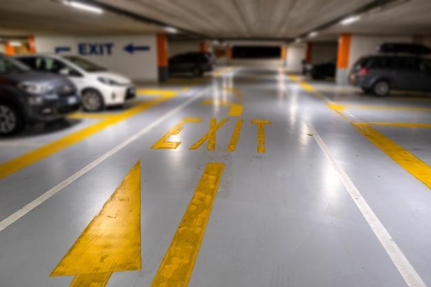 Желтая маркировка с размытыми современными автомобилями, припаркованными внутри закрытой подземной автостоянки.