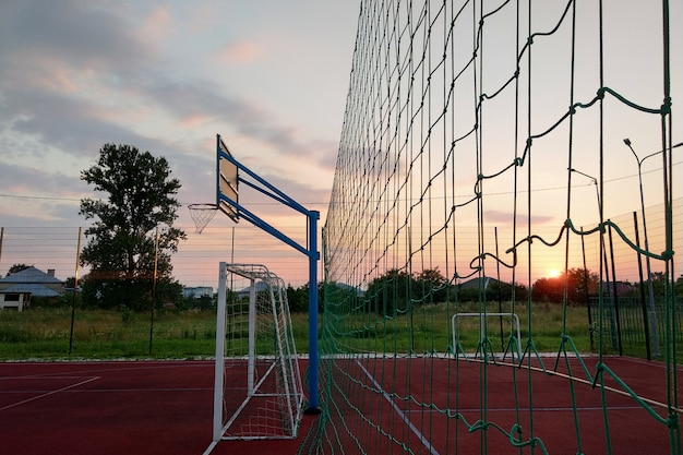 На открытом воздухе площадка для мини-футбола и баскетбола с воротами для мяча и корзиной, окруженной высоким защитным забором.
