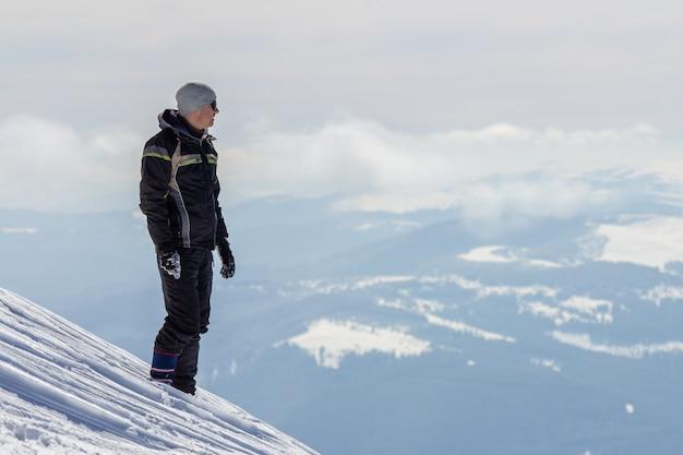 明るく晴れた冬の日にビューと達成を楽しんでいる雪に覆われた山の頂上に立っている一人の観光客のシルエット。冒険、野外活動、健康的なライフスタイルのコンセプト。