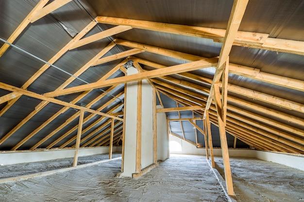 Чердак здания с деревянными балками конструкции крыши.