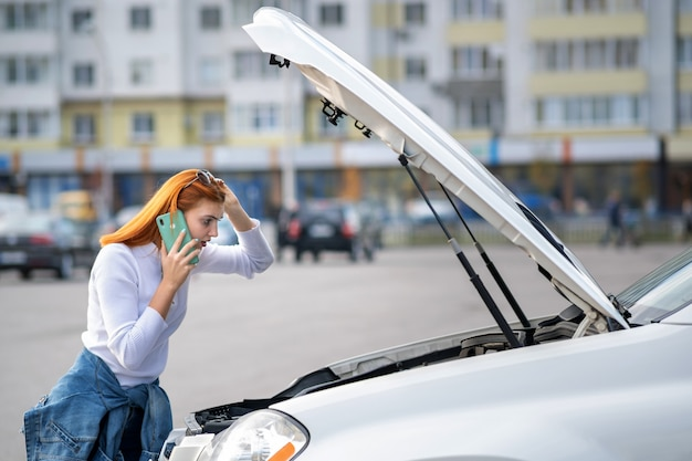 助けを待っている間彼女の携帯電話で話している飛び出るフード付きの壊れた車の近くに立っている若い女性。