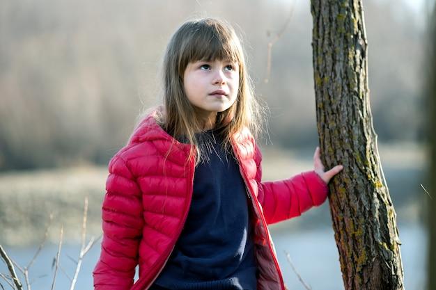 秋の屋外で木の幹の近くに立っているかわいい子少女の肖像画。
