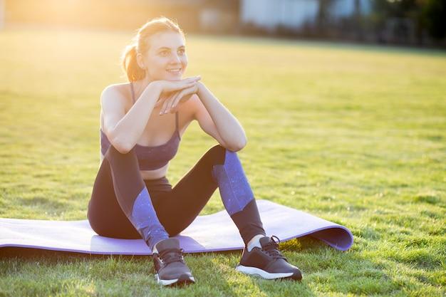 日の出フィールドでの演習を行う前にトレーニングマットの上に座ってスポーツ服の若い陽気な女性。