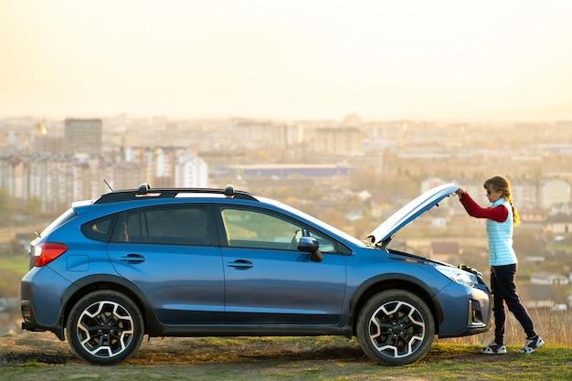 壊れた車のボンネットを開く若い女性は彼女の車に問題があります。フードのポップアップで自動車の近くに立っている女性ドライバー。