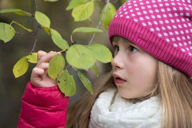 かわいい子の女の子は、屋外の寒さで緑の葉と木の枝を保持している暖かい冬の服を着ています。