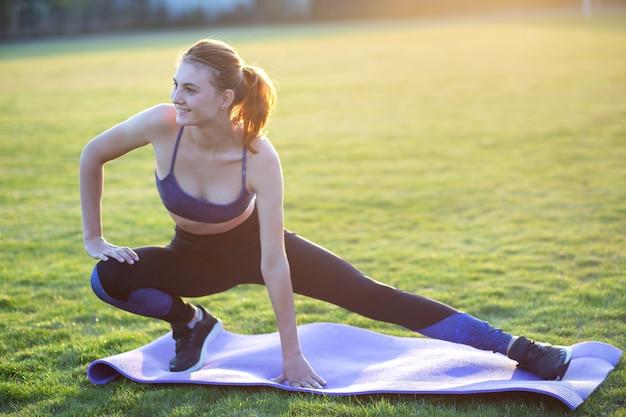朝の野外で実行する前に運動をしている若い陽気な女性。