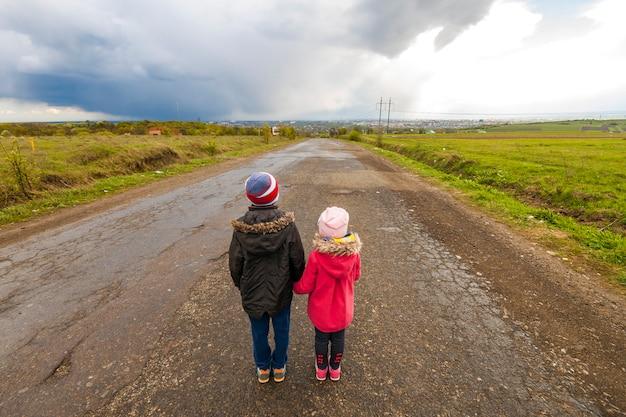 Двое маленьких детей мальчик и девочка гуляют по дороге