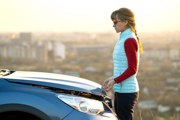 壊れた車のボンネットを開く若い女性は彼女の車に問題があります。フードがポップアップした自動車の近くの女性ドライバー。