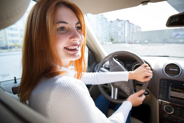 Молодой рыжий женщина водитель за рулем вождения автомобиля, счастливо улыбается.