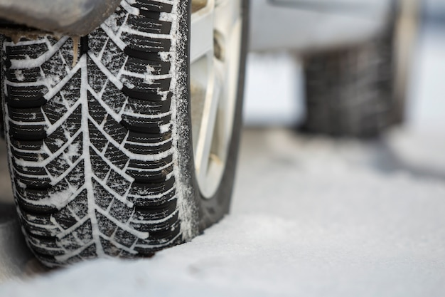 冬の日に雪道に駐車した車のタイヤのクローズアップ。輸送と安全のコンセプトです。