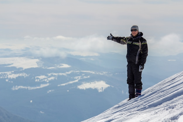 勝者の雪に覆われた山の頂上に立っている一人の観光客のシルエットは明るい晴れた冬の日にビューと達成を楽しんでいる上げられた手でポーズします。冒険、野外活動、健康的なライフスタイル。