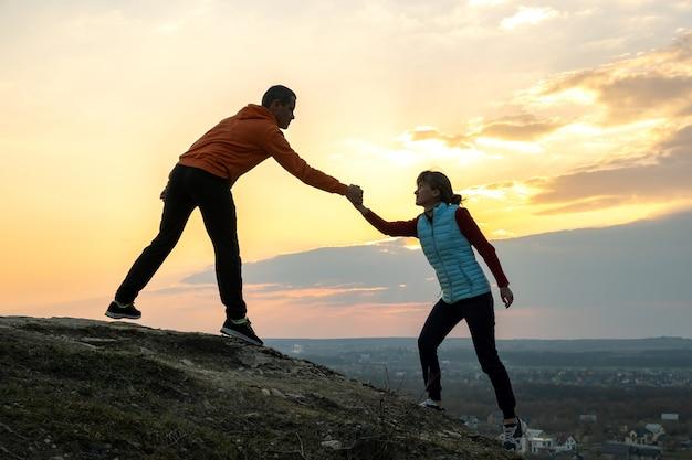 Мужчина и женщина туристов, помогая друг другу подняться камень на закате в горах. пары взбираясь на высоком утесе в природе вечера. туризм, путешествия и концепция здорового образа жизни.
