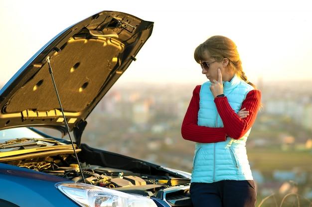 フードがポップアップした故障した車の近くに立っている若い女性は、彼女の車に問題があります。