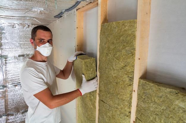 木製フレームの壁にロックウール断熱材の人工呼吸器の若年労働者