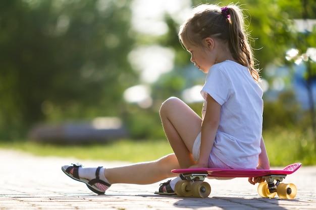 スケートボードの上に座って白い服でかなり小さな長い髪のブロンドの女の子の横顔の肖像画