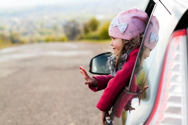車の窓を通して見る車の中でかわいい女の子。旅行のコンセプト。