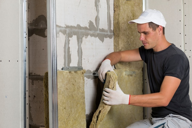 木製フレームのロックウール断熱材を保護する保護手袋の労働者