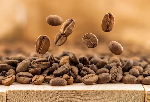 コピースペースを背景として新鮮なコーヒー豆を飛んでください。