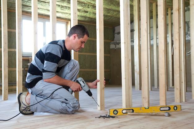 若いプロの労働者は、将来の壁にレベルとドライバーを使用して木製フレームを取り付けます