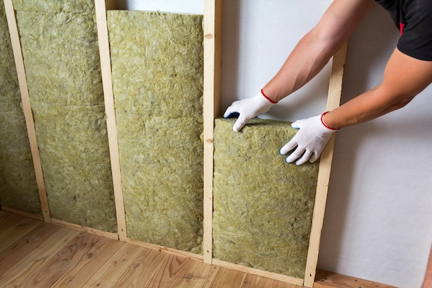 コールドバリアの将来の壁のための木製フレームのロックウール断熱スタッフを絶縁する白い手袋で労働者の手のクローズアップ。快適な暖かい家、経済、建設、改修のコンセプト。