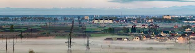 遠くのカルパティア山脈の濃い朝の霧の下で春の野原と木々の間を地平線まで伸びる長い電気高圧送電線の行の美しいパノラマ。