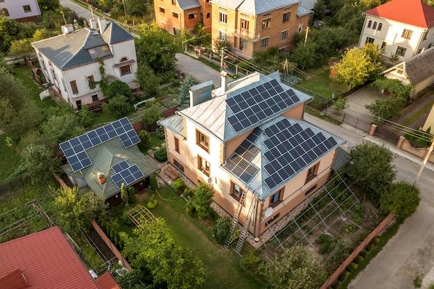屋根の上の青い光沢のある太陽光写真太陽光発電パネルシステムと新しいモダンな住宅コテージの空中の平面図。再生可能な生態学的なグリーンエネルギー生産の概念。