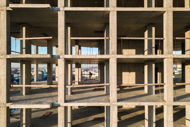 Вид с воздуха на бетонный каркас высокого жилого дома под строительство в городе.