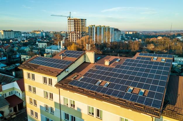 産業用建物の屋根に取り付けられた多くの太陽光発電太陽電池パネルの航空写真。