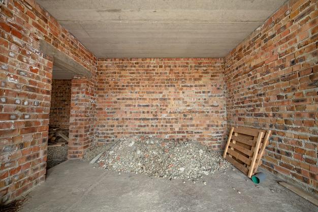 未完成のれんが造りの家の内部。コンクリートの床と裸壁で、左官工事の準備ができています。不動産開発