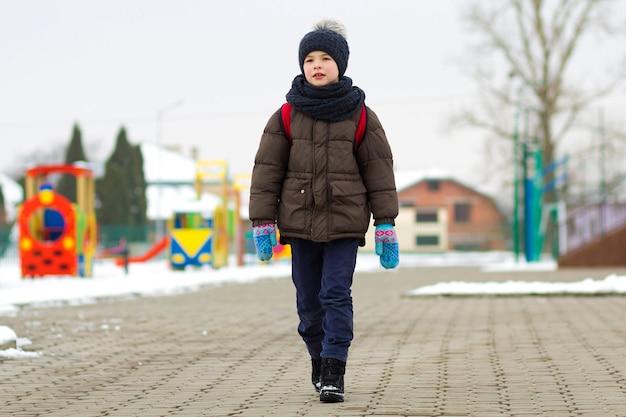 公園を歩いている少年。冬にランドセルを持って放課後散歩に行く子。新鮮な空気の屋外での子供の活動。健康的な生き方のコンセプト。