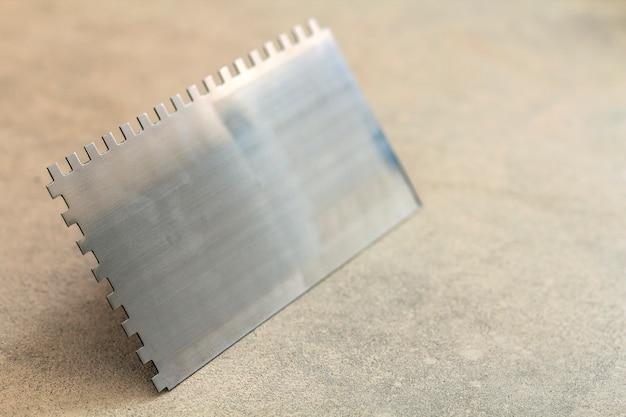 ノッチ付きコテはタイル設置工事用工具