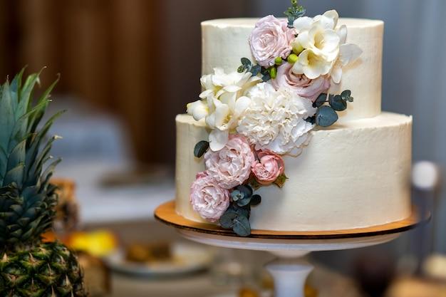 Высокий сладкий свадебный торт украшен розовыми и белыми цветами на столе.