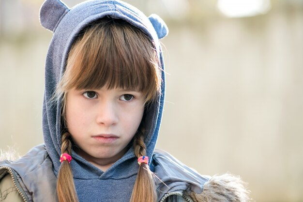 Портрет девушки счастливого ребенка в теплой одежде осенью на открытом воздухе.