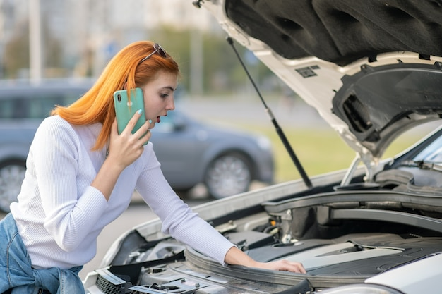 彼女の携帯電話で話している飛び出るフード付きの壊れた車の近くに立っている若い女性。