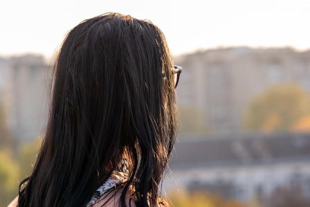 都市景観を探しているメガネの女性の背面図。