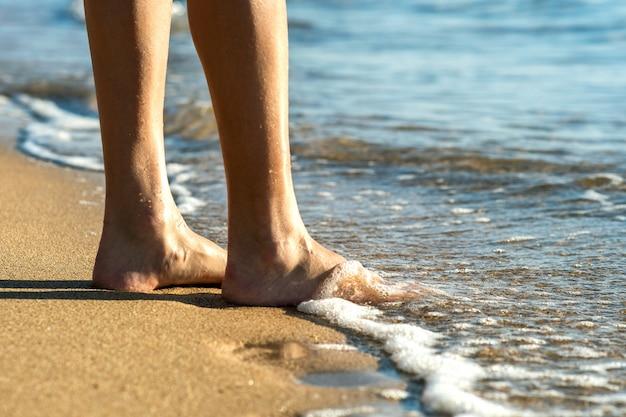 海の水の砂浜で裸足で歩く女性の足のクローズアップ。