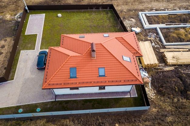 В доме металлическая черепичная крыша с мансардными окнами и черный автомобиль.