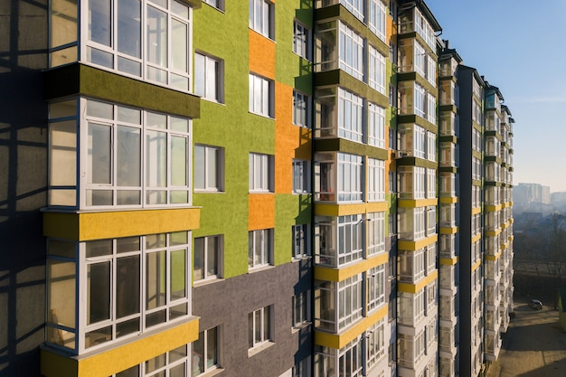 Высокий жилой многоквартирный дом с множеством окон и балконов.