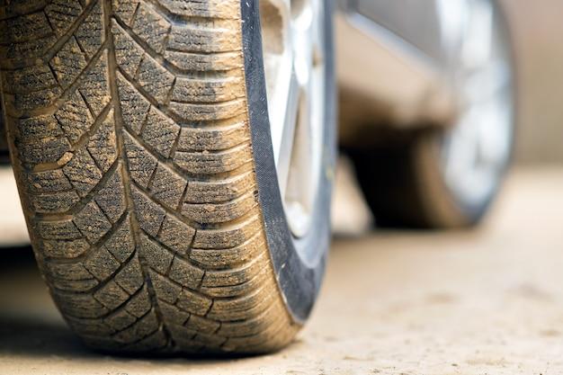 ゴム製タイヤで汚れた車のホイールのクローズアップ。