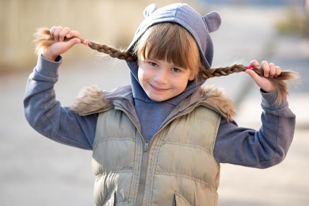 Портрет счастливой девочки ребенка с косами волос.
