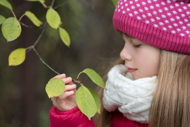 かわいい子少女は、屋外の寒さで緑の葉と木の枝を保持している暖かい冬の服を着ています。