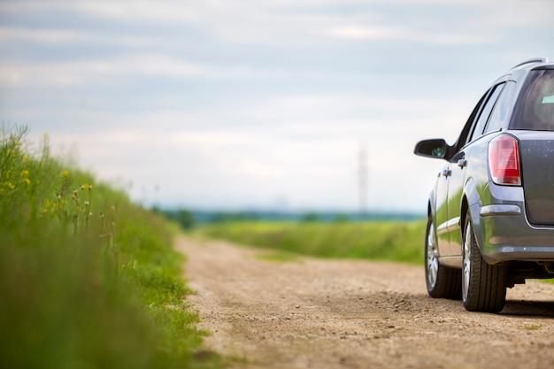緑の野原の未舗装の道路上の車。