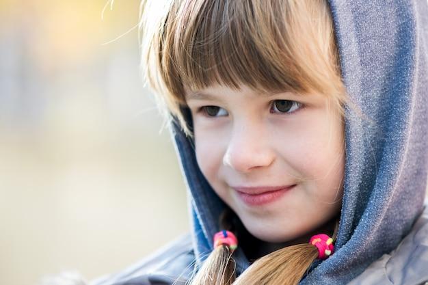 Портрет девушки счастливого ребенка в теплую одежду на открытом воздухе.