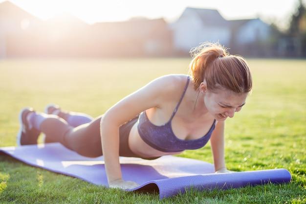 Молодая спортивная женщина в спортивной одежде, обучение в поле на рассвете.