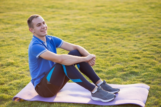 朝のフィールドでトレーニングマットの上に座っている陽気な若者。