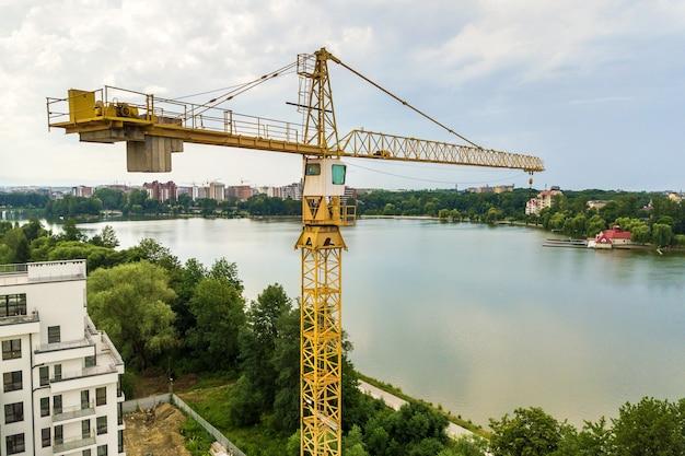 Аэрофотоснимок подъемного крана башни и бетонный каркас жилого дома высокой квартиры под строительство в городе. концепция городского развития и роста недвижимости.